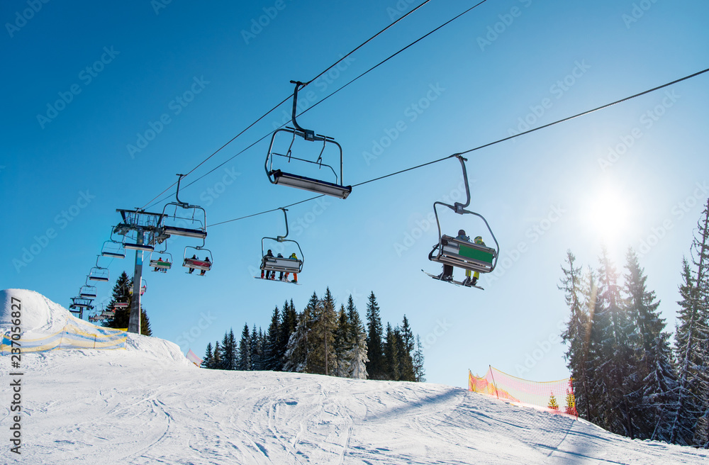Fototapety, obrazy: Low angle shot of a ski lift at ski resort Bukovel in the mountains on a sunny winter day. Blue sky, sun and forest on the background copyspace riding top nature extreme sport recreation concept