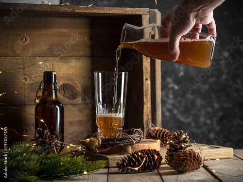 Tuinposter Bier / Cider pouring beer into a tall glass on wooden background with christmas lights