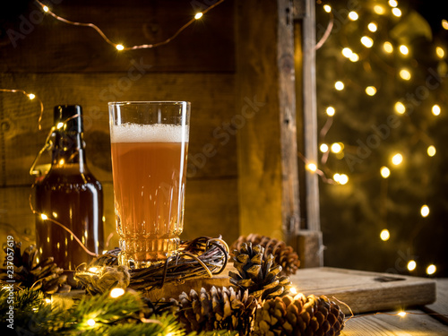 Door stickers Beer / Cider Beer in glass on wooden background with Christmas lights and pine cones