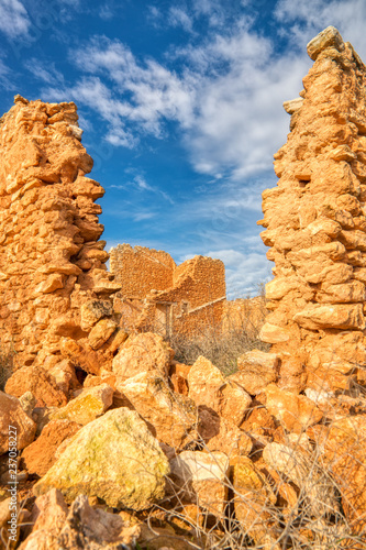 A Vertical Photo Of The Ruins Of An Old Stone House Looking