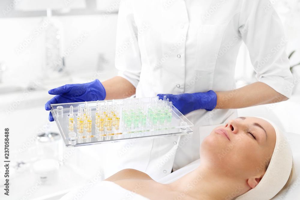 Fototapeta Ampułki kosmetyczne. Kosmetyczka trzyma w dłoni tace z  preparatami do kosmetycznymi.