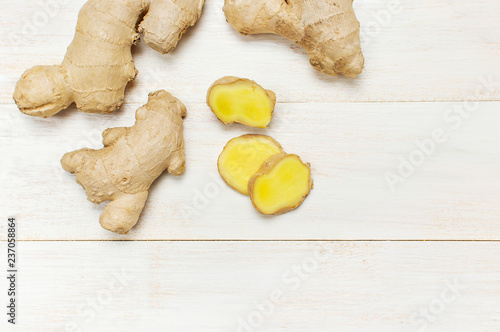 Whole and sliced fresh ginger roots on white wooden background top view copy space. Minimalistic style, seasoning, spice, ingredient for tea. Concept healthy food, medicine, improving immunity