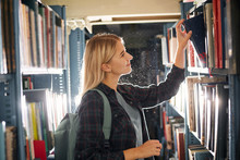 Blonde Caucasian Young Woman Searching Book In The Old Bookstore Walking Along Long Rows Of Bookshelves Picking Out Something Unusual For Gift To Her Boyfriend