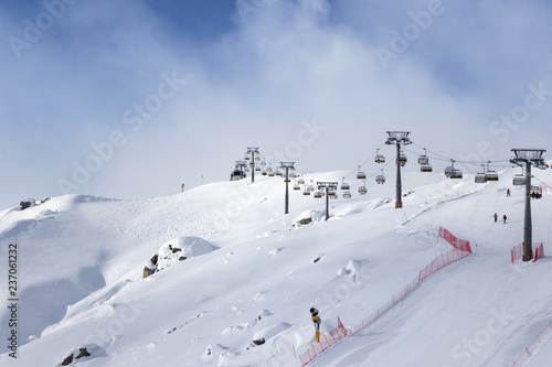 Snowy ski slope and ski-lift at ski resort at sunny winter evening