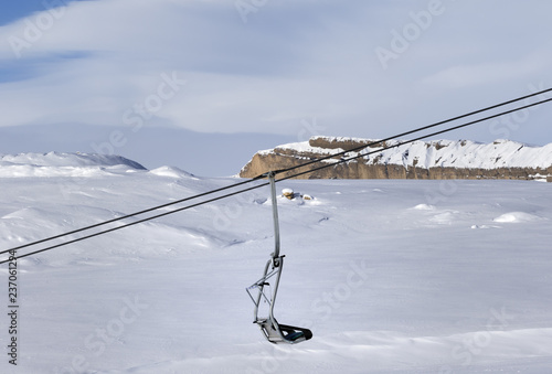 Snowy slope, chair-lift and cloudy sky at cold winter day