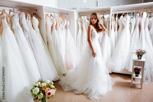 Pinturas sobre lienzo  Back view of a young woman in wedding dress looking at bridal gowns on display i