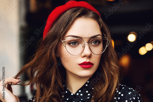 Close up portrait of young beautiful fashionable woman with red lips makeup, long hair, wearing stylish transparent glasses, red beret, polka dot blouse. Lights on background.