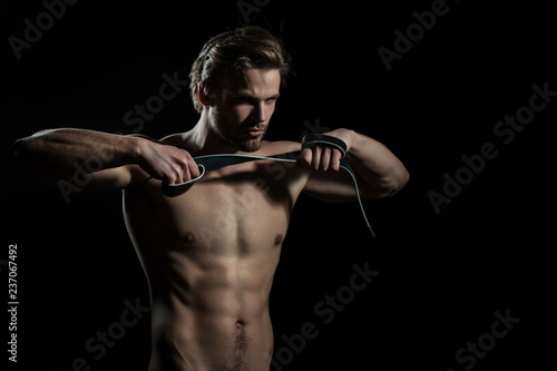 Belt in hands of naked man. The guy does exercises for hands with leather belt. Sexy model for men's accessories. Concentration and meditation in the gym - 237067492