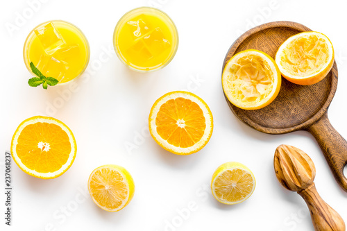 Fototapety, obrazy: Squeeze fresh oranges with juicer. Orange juice in glass near half cut oranges on white background top view