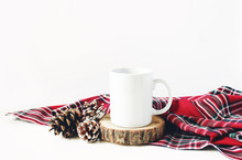 Winter Still Life Composition. Blank Ceramic Coffee Mugstanding On Wooden Cut Board, Pine Cones And Red Checkered Tartan Plaid On White Table Background. Christmas Traditional Styled Photo, Mockup.