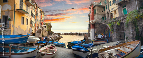 Street with fishing boats and view of bay in village of Riomaggiore at sunset. Liguria, Italy