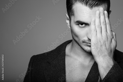 Intense black&white portrait of handsome young man with stylish haircut posing over gray background. Perfect hair & skin. Close up. Studio shot