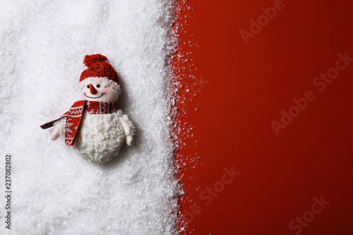 Fototapeta Composition with small decorative snowman on color background, top view