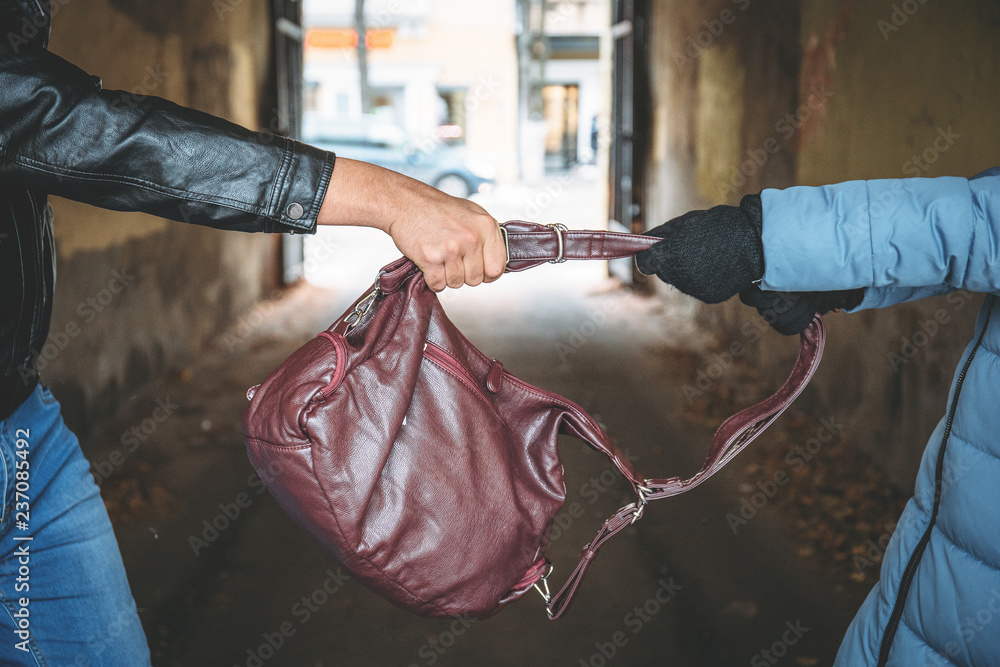Fototapeta Robber snatches bag from hands of woman, close up. Criminal pickpocket and crimes on city street