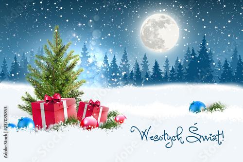 Fototapeta Koncepcja kartki świątecznej z napisem Wesołych Świąt po polsku. Zimowa nocna sceneria z księżycem w tle, w śniegu leżące koło choinki prezenty oraz porozrzucane bombki. Na niebie widać padający śnieg obraz