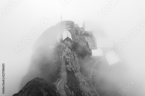 Fotografía  Group of mountain cottages barely visible in thick clouds