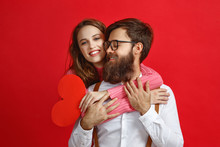 Valentine's Day Concept. Happy Young Couple With Heart, Flowers, Gift On Red