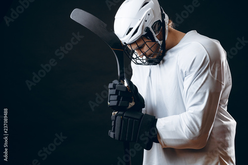 Caucasian American hockey player, in white uniform and helmet, isolated on black, prays for good luck, wishes triumph and victory.