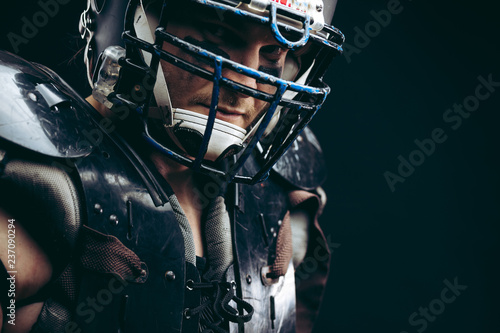Portrait of american football player with ball wearing helmet and protective shields looking at camera isolated over black background, close up
