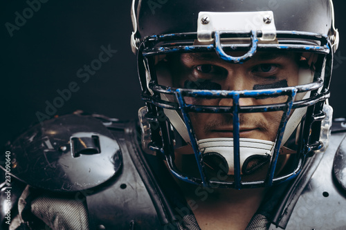 Face portrait of manly loooking young sportsman in black protective headgear and armour, looking courageously at camera, determined to win