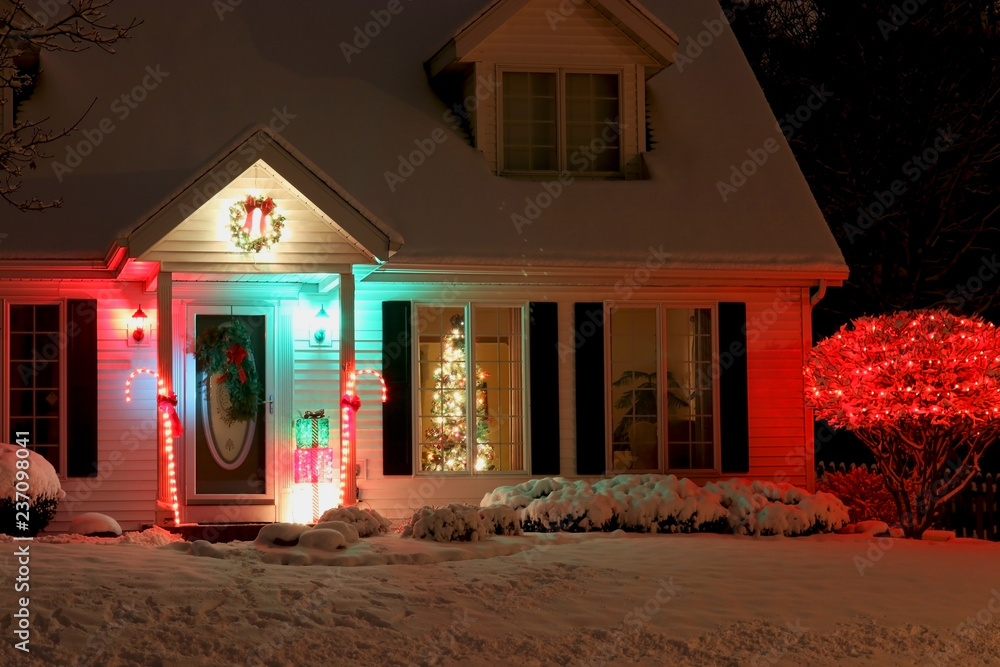 Fototapeta Seasonal house outdoors decoration. Background with house main entrance and front yard, covered by fresh snow decorated for Christmas and New Year Holidays. Decorated christmas tree in the window.