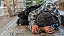 Poor Homeless Beggar Sleeping On Pathway Floor In Suffering Of Unemployment Asking For Help