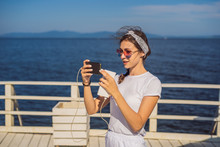 Cruise Ship Woman Using Mobile Phone On Travel Vacation At Ocean. Girl Texting Sms On Wifi On Tropical Holidays. Internet On International Seas Concept. Tourist Looking At Her Holiday Pictures