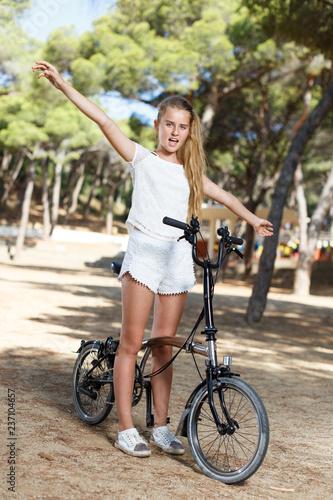 Fotografie, Obraz  Emotional  teen girl standing near bike ready to go on park ride