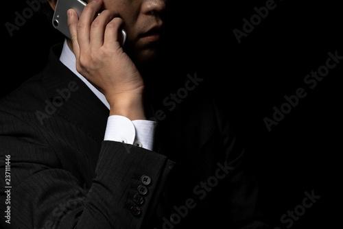 Photo スマートフォンで電話をかけるビジネスマン