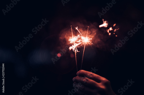 Hand holding burning Sparkler blast on a black bokeh background at night,holiday celebration event party,dark vintage tone Canvas Print