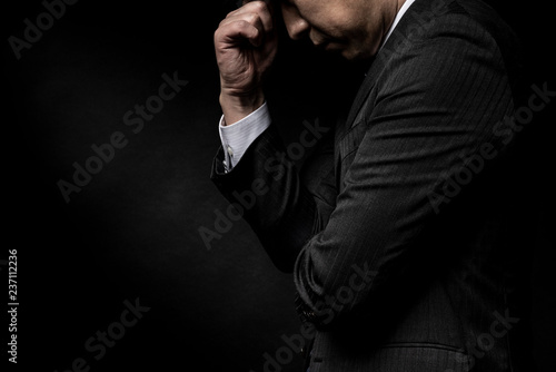 Photo 頭を抱えて悩む男性