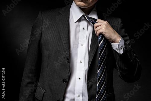 Fotografering ネクタイを緩めるスーツ姿の男性