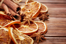 Dry Orange Slices, Cinnamon Sticks And Anise On Wooden Background