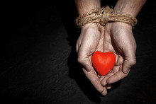 Man With Hands Tied Rope And Heart In His Palms On Black Background. Love Concept Binds Hands. Copy Space For Text.