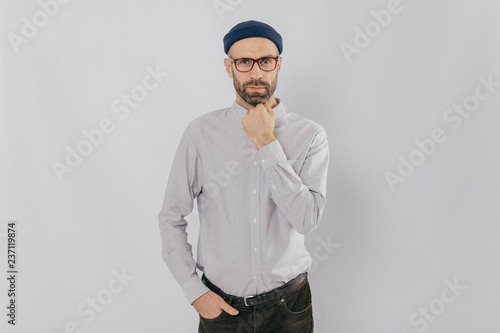Fotografía  Waist up shot of serious man keeps one hand under chin, other in pocket, has stubble, wears hat, white shirt, trousers, isolated over white background, listens something attentively