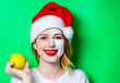 canvas print picture - Woman using eye patch for her eyes in Santa Claus hat with cream on her face and holding an apple. Portrait of natural  and true female as usually they are looks like
