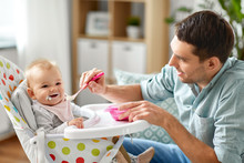 Family, Food, Eating And People Concept - Happy Father Feeding Little Baby Daughter Sitting In Highchair With Puree By Spoon At Home