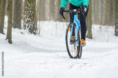 Obraz Cyclist on cyclocross bike trails in the snowy forest in winter. Downhill riding a snowy slope. Winter workout outdoors concept - fototapety do salonu