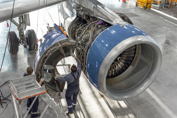 Technical specialists and aircraft technicians install the reverse engine after scheduled service. Concept maintenance of airplane.