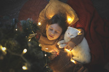 Cat And Kid Sleeping Together Under Christmas Tree