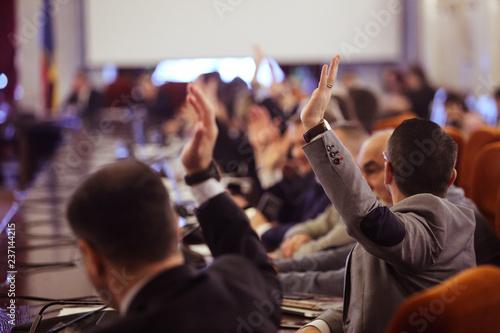 Fotografie, Obraz Members of Parliament voting by raising hands
