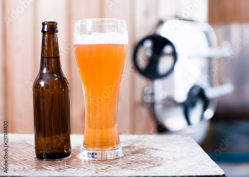 Tuinposter Bier / Cider bottle and glass with gold beer on the background of barrels for fermentation