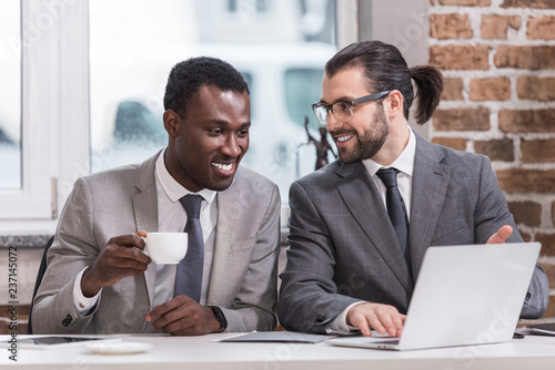 Fototapeta smiling multicultural businessmen drinking coffee and looking at laptop in office obraz na płótnie