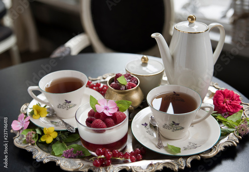 Fotografie, Obraz  Tea in old porcelain cups, panakota dessert and raspberry on an old silver tray