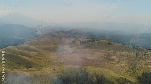 Foto op Aluminium Blauw aerial view forest fire smoke on slopes hills. wild fire in tropical forest, Java Indonesia. natural disaster fire in Southeast Asia