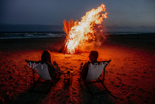 Romantic Mature Couples Watch The Sea In Front Of Campfire At Night