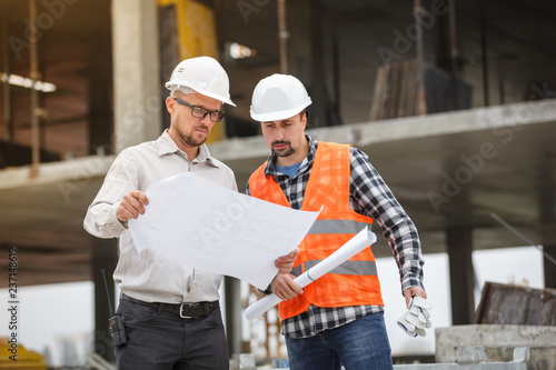 Fotografía  Male architect and developer discussing blueprints at construction site