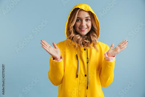 Obraz Image of joyful woman 20s wearing yellow raincoat looking at camera, isolated over blue background - fototapety do salonu