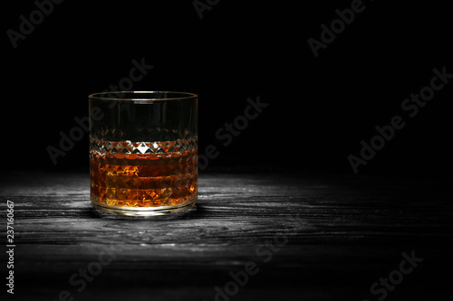 Glass of whisky with ice on wooden table against black background Canvas Print
