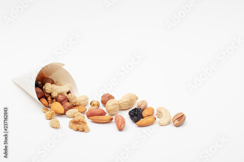 Assorted  Nuts  spill out of a paper cone on white background Canvas Print